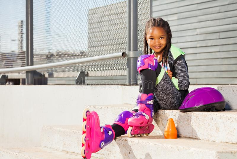 直排轮式溜冰鞋的女孩坐台阶 免版税库存照片