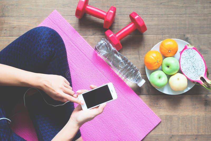 直接地上面健身衣物的妇女使用手机用运动器材和果子在地板上,健康 免版税库存照片
