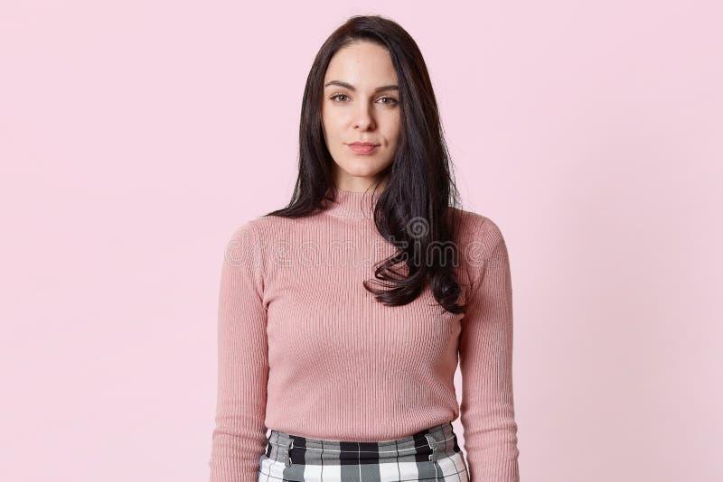 直接悦目苗条严肃的模型身分接近的画象在演播室,佩带的套头衫的浅粉红色的背景和 库存照片