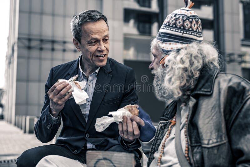 直言善良男人谈话与灰发的资深无家可归者 免版税图库摄影