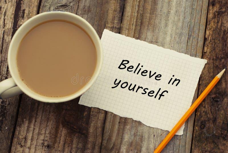 相信你自己在白色papper的题字 在土气木背景的杯cofee和铅笔 库存照片