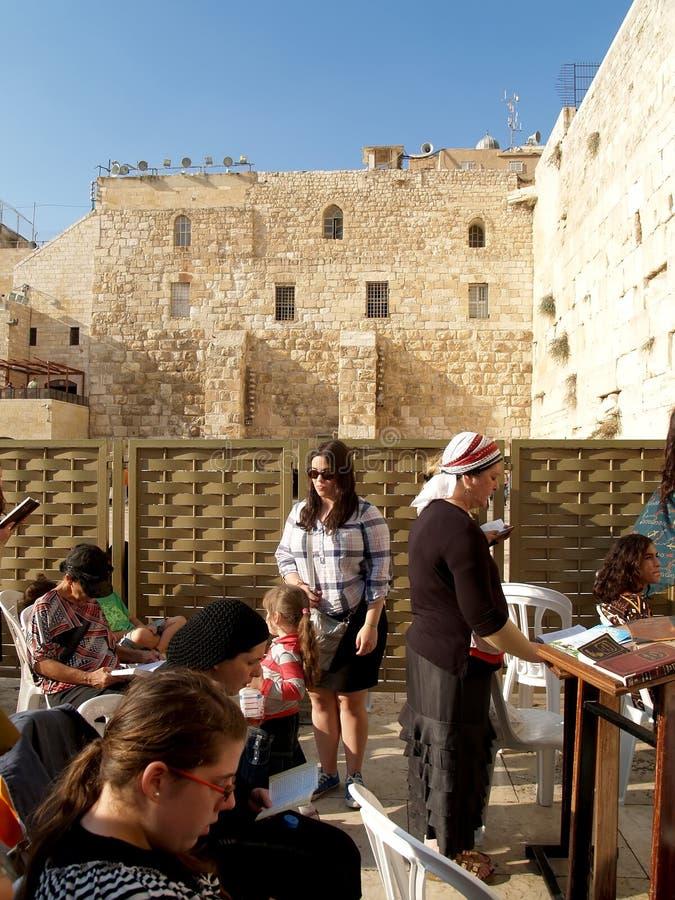 相信的妇女在哭墙前读了宗教书 库存图片