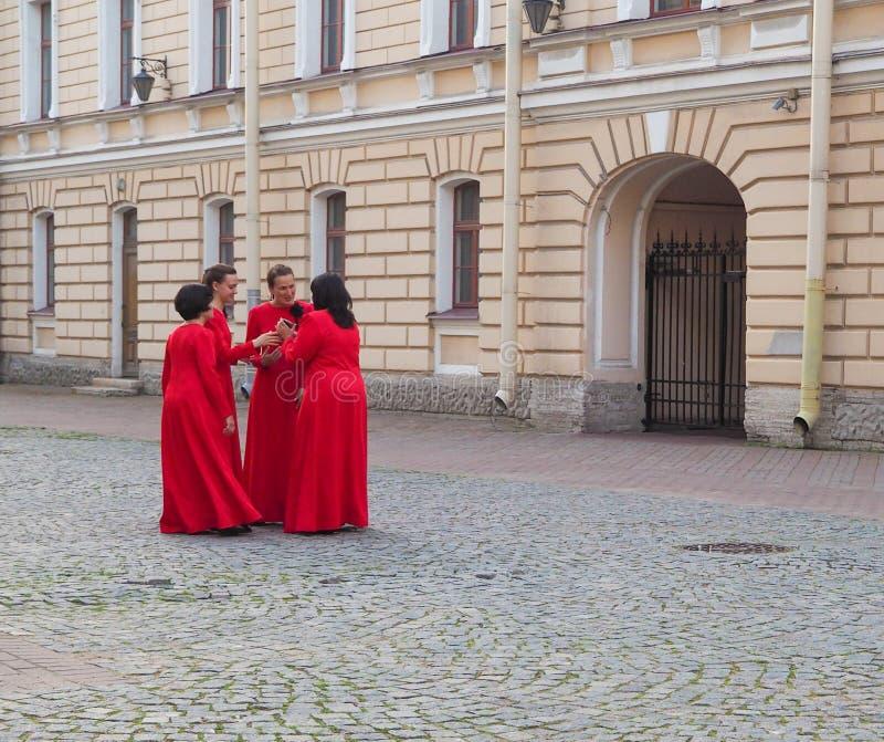 相同红色礼服的几名妇女在圈子谈话互相会集 圣彼德堡 夏天2017年 免版税库存照片