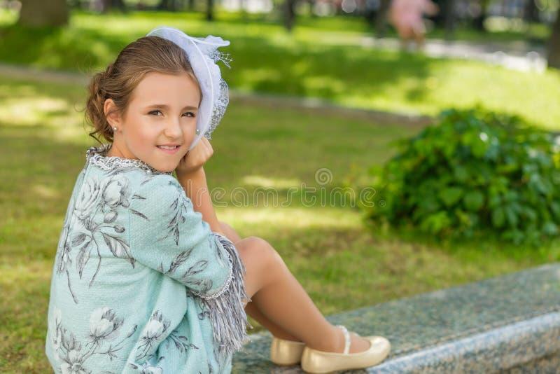 相当一件俏丽的葡萄酒礼服的棕色目的女孩 库存图片