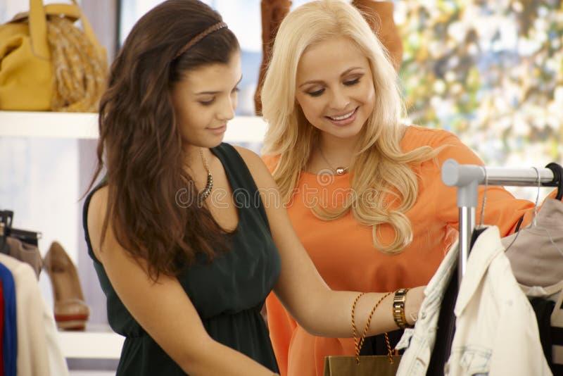 购物在衣裳商店的俏丽的女孩 图库摄影