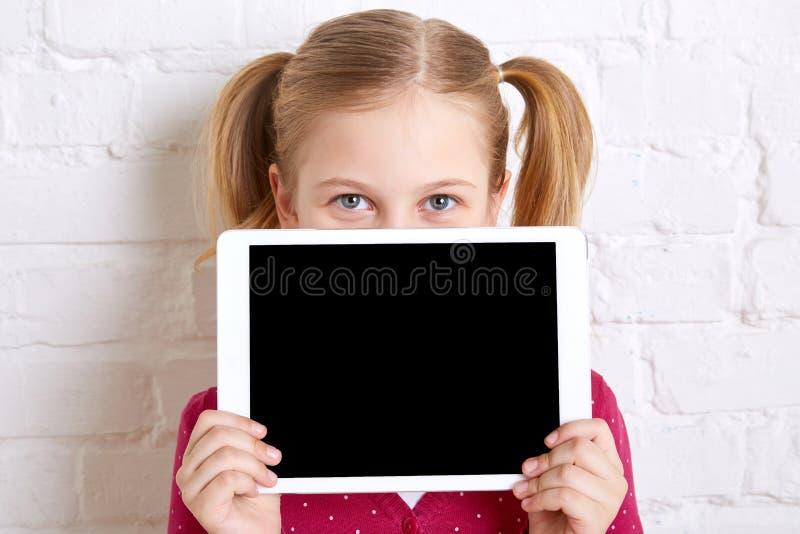 相当举行和掩藏在膝上型计算机后的小女孩 复制空间 免版税图库摄影
