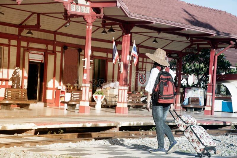 相当亚洲妇女旅客背包徒步旅行者步行和阻力,在一个火车站的下落行李 免版税库存图片