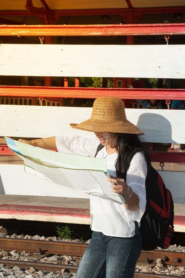 相当亚裔在火车站的旅客背包徒步旅行者女性看的地图 免版税库存照片