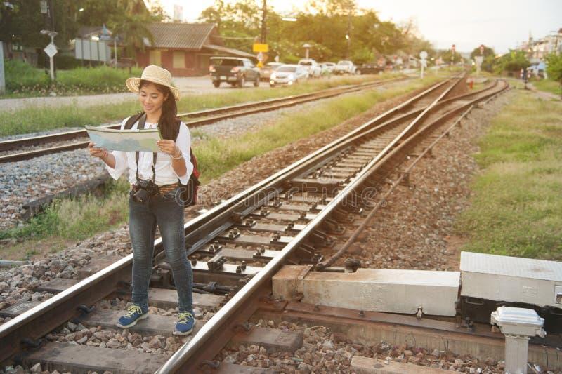相当亚裔在火车站的旅客背包徒步旅行者女性看的地图 图库摄影