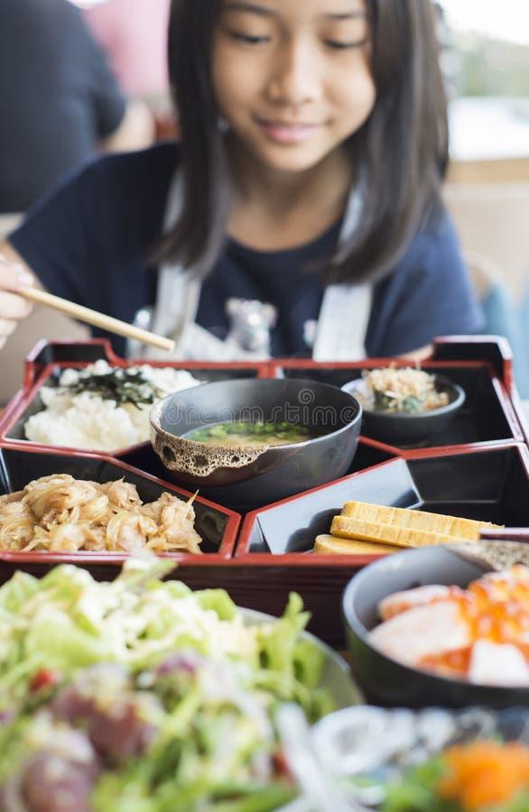 相当亚裔女孩在Bento午餐盒享用日本食物 库存图片