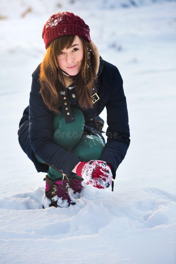 相当亚裔妇女在她的手上的拿着自然软的白色雪做雪球,微笑在一个冷的冬日期间在森林里 图库摄影