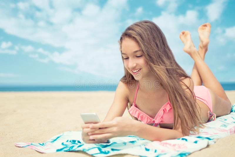相当使用一个巧妙的电话的十几岁的女孩说谎在与海的海滩和天际在背景 图库摄影