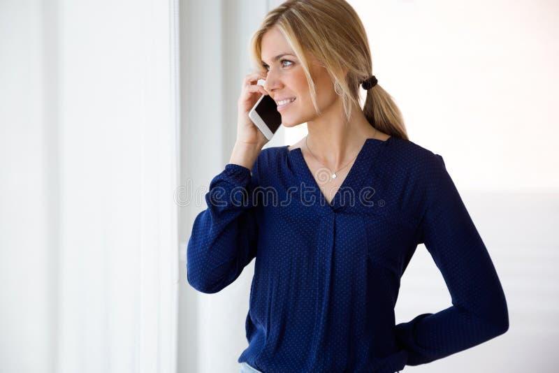 相当使用她的手机的少妇,当在家时站立在客厅 免版税库存图片