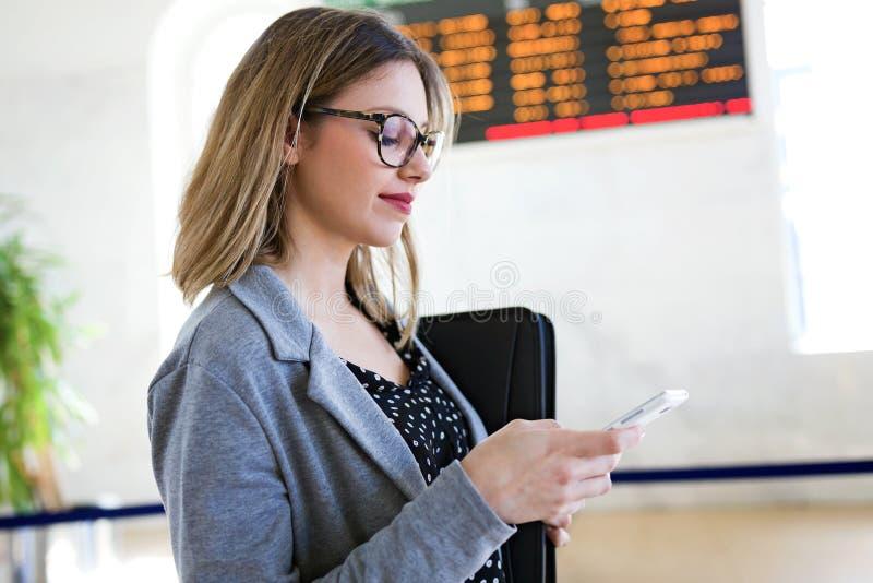 相当使用她的手机的年轻女商人在火车站 免版税库存图片