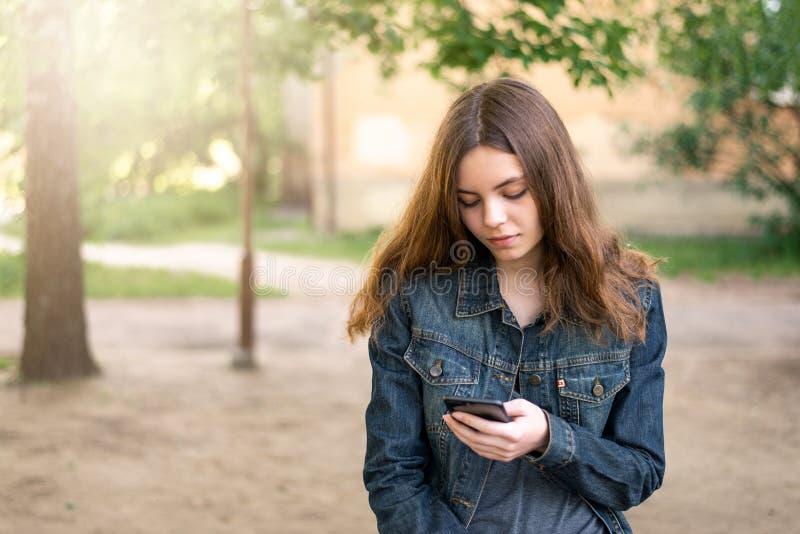 相当使用电话的青少年的女孩在社会媒介 免版税库存图片