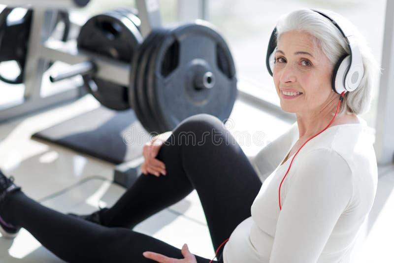 相当使用耳机的资深妇女在健身房 图库摄影