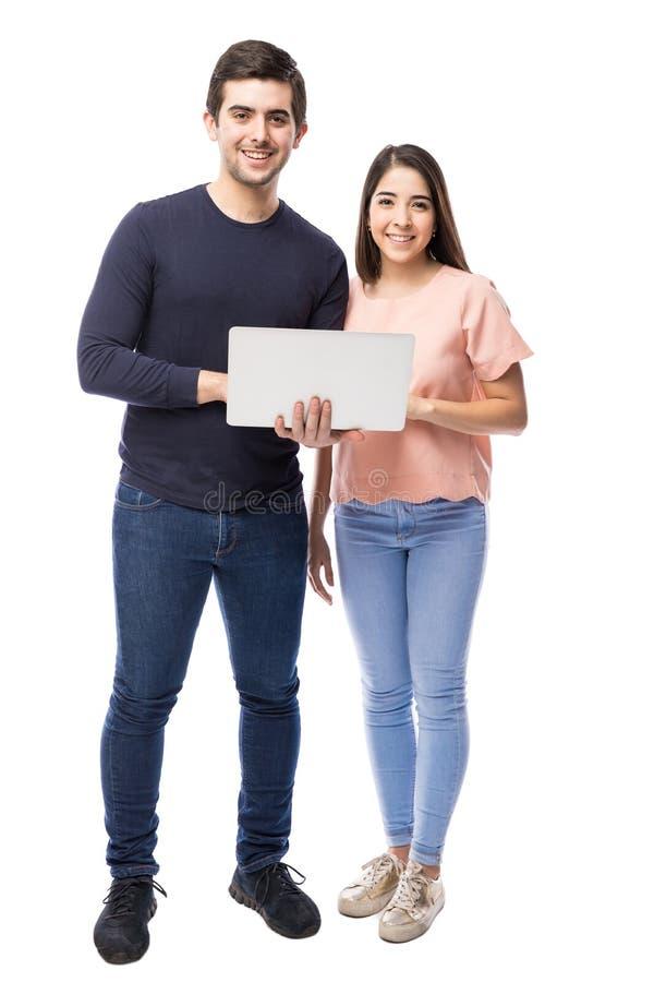 相当使用膝上型计算机的拉丁夫妇 免版税库存照片