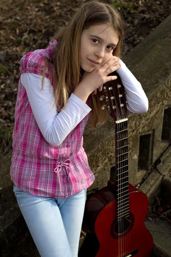 相当倾斜在吉他的女孩微笑和看照相机户外 免版税库存照片