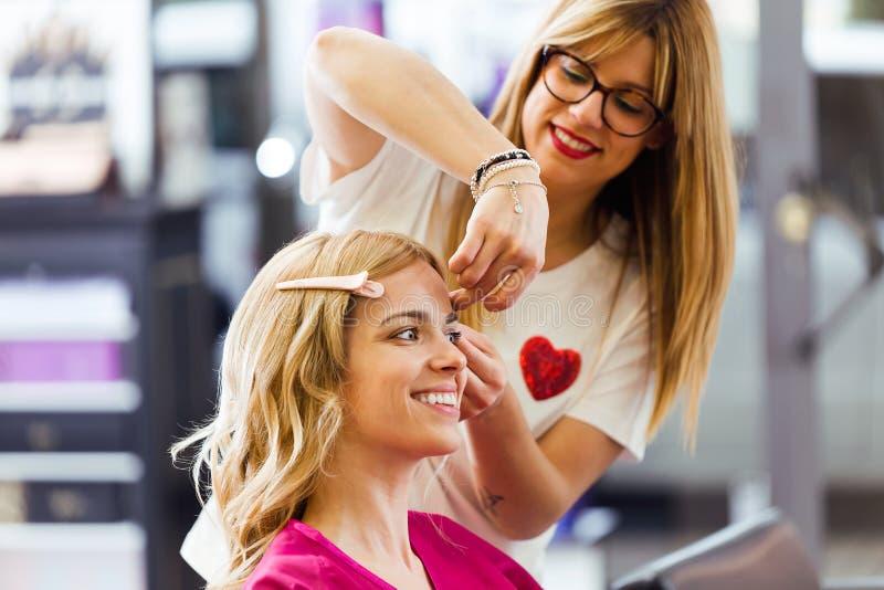 相当做发型的年轻美发师对美容院的逗人喜爱的妇女 图库摄影