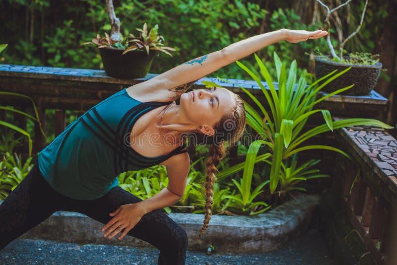 相当做瑜伽外面在自然环境里的少妇 库存图片