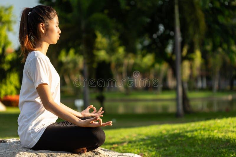 相当做瑜伽的亚裔妇女在公园行使 库存照片