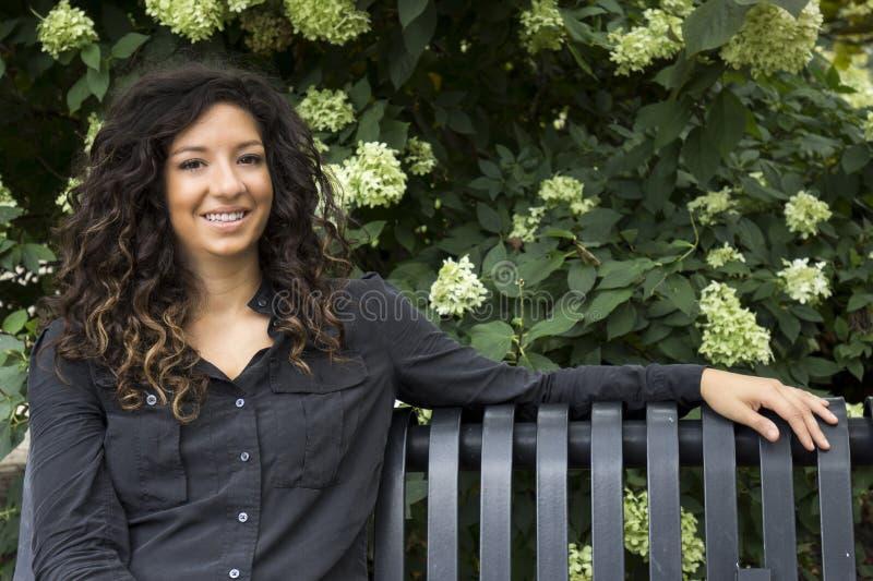 相当公园长椅微笑的卷发的妇女 库存图片