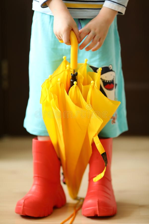 相当凉快rainboots五颜六色的穿戴和伞的孩子 图库摄影