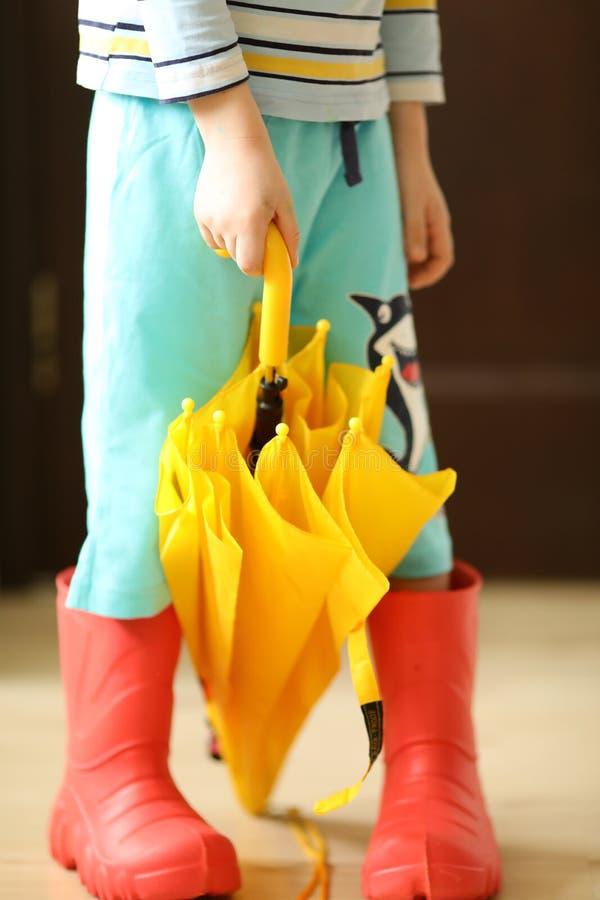相当凉快rainboots五颜六色的穿戴和伞的孩子 库存图片