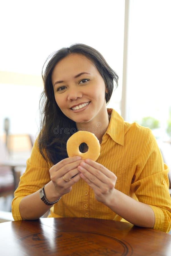 相当吃多福饼的年轻可爱的妇女在Caf 库存照片