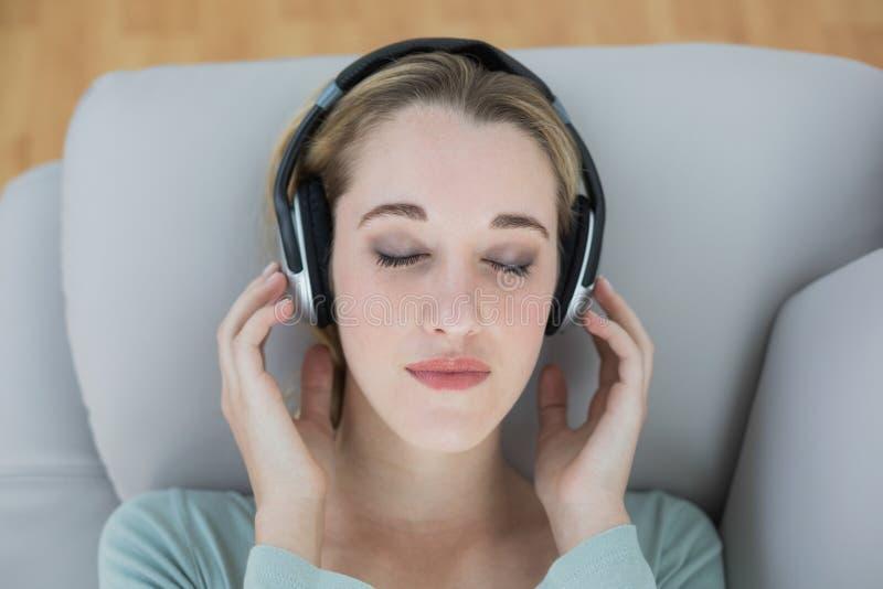 相当听与耳机的自然妇女到说谎的音乐  库存图片
