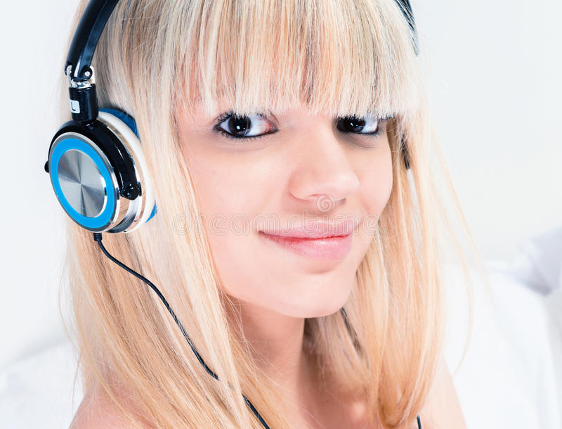 相当听到在她的smartphone的音乐的白肤金发的女孩 免版税库存图片