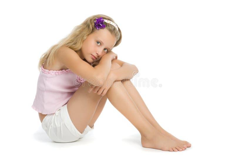 相当哀伤楼层的女孩坐少年 免版税库存图片