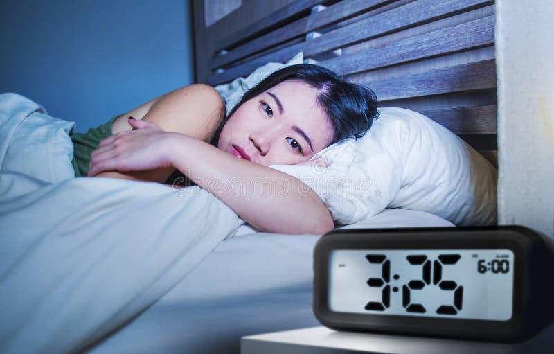 相当哀伤的年轻人和醒沮丧的亚裔韩国的妇女有说谎失眠的混乱在床失眠的遭受的忧虑depressi 库存图片