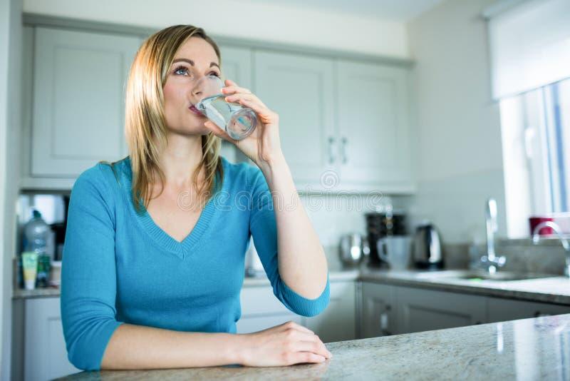 相当喝一杯水的白肤金发的妇女 免版税库存图片