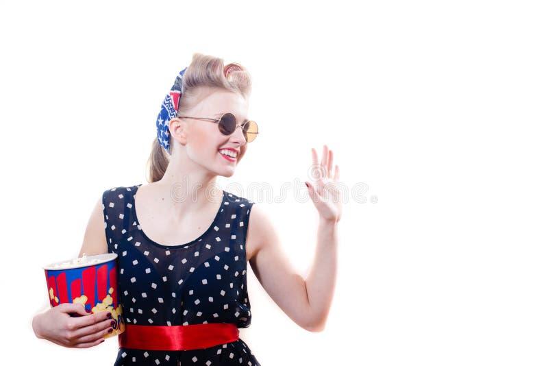 相当圆点礼服的滑稽的年轻白肤金发的画报妇女有与玉米花愉快微笑&挥动的卷发的人圆的太阳镜的 库存图片