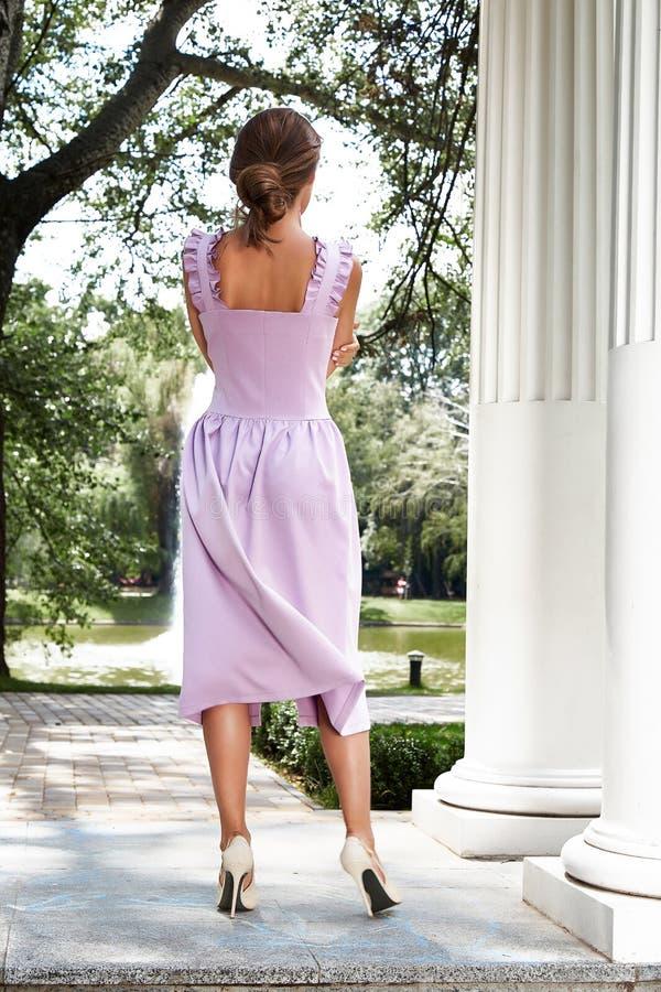 相当在公园专栏博士的性感的夫人魅力时装模特儿步行 免版税库存图片