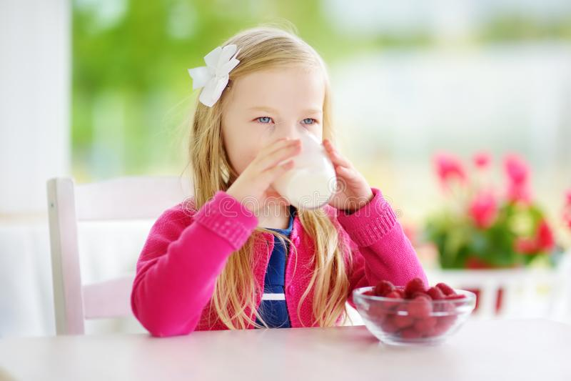 相当在家吃莓和饮用奶的小女孩 享用她的健康新鲜的有