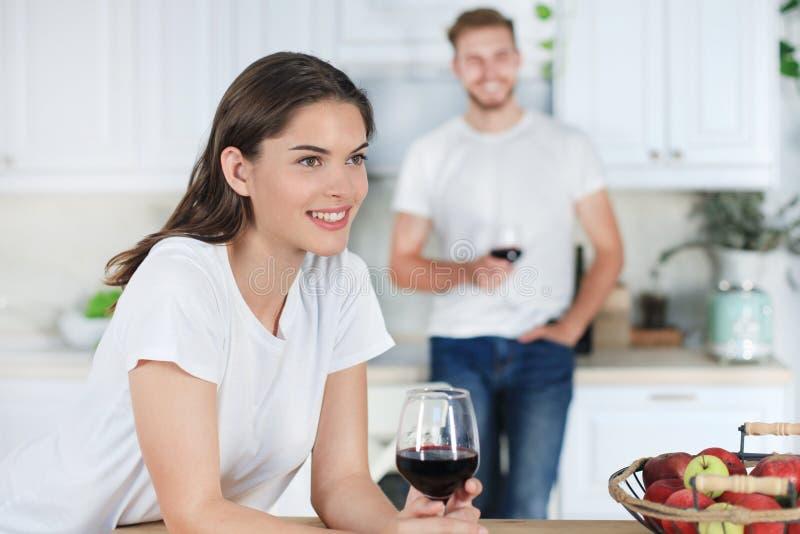 相当在家喝一些酒的少妇在厨房里 库存照片