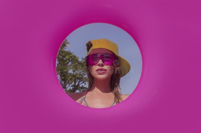 相当在桃红色可膨胀的圆环中间的年轻bikni妇女 免版税库存图片