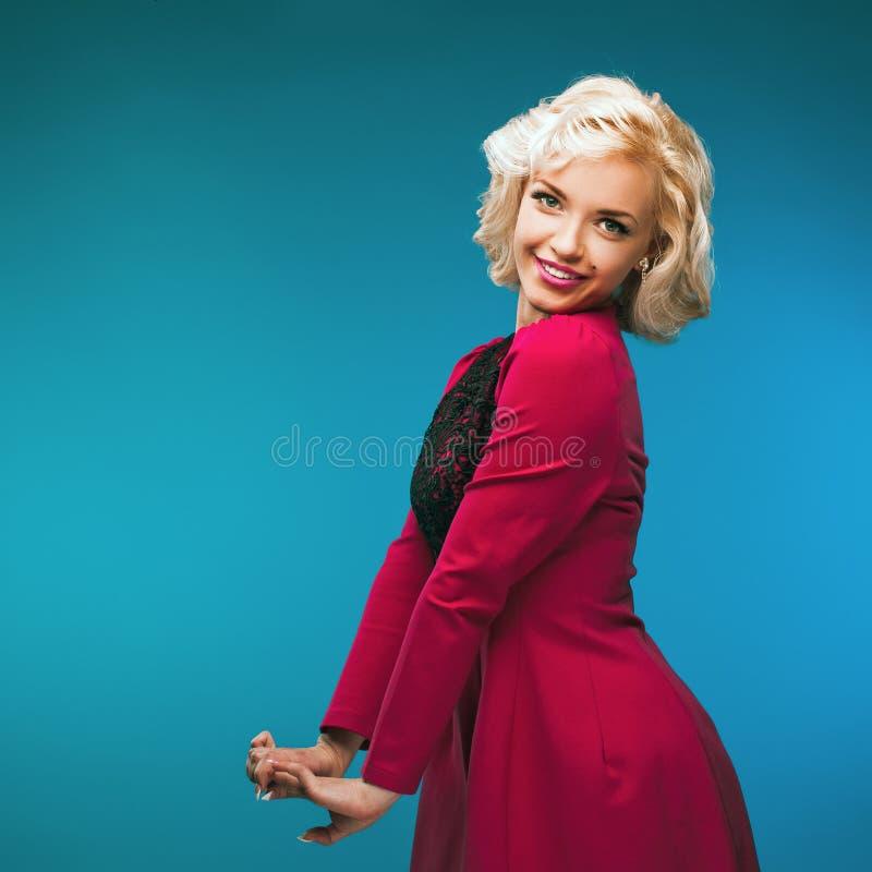相当在桃红色礼服的白肤金发的女孩模型 葡萄酒 免版税库存照片