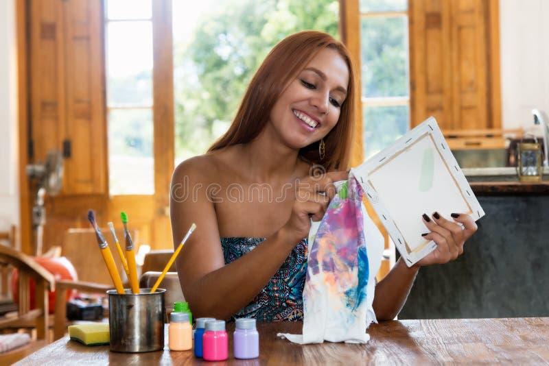 相当在演播室的女性艺术家绘画 免版税库存图片