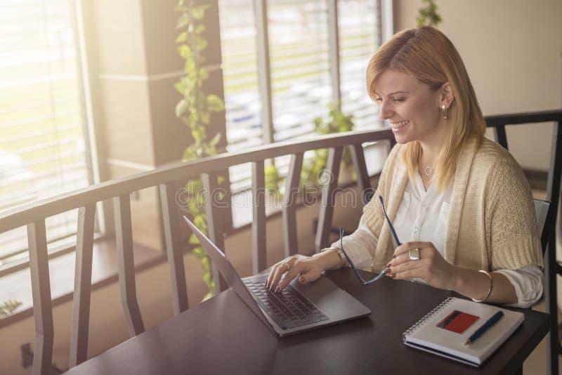 相当在网上购物使用她的信用卡和膝部的少妇 库存照片
