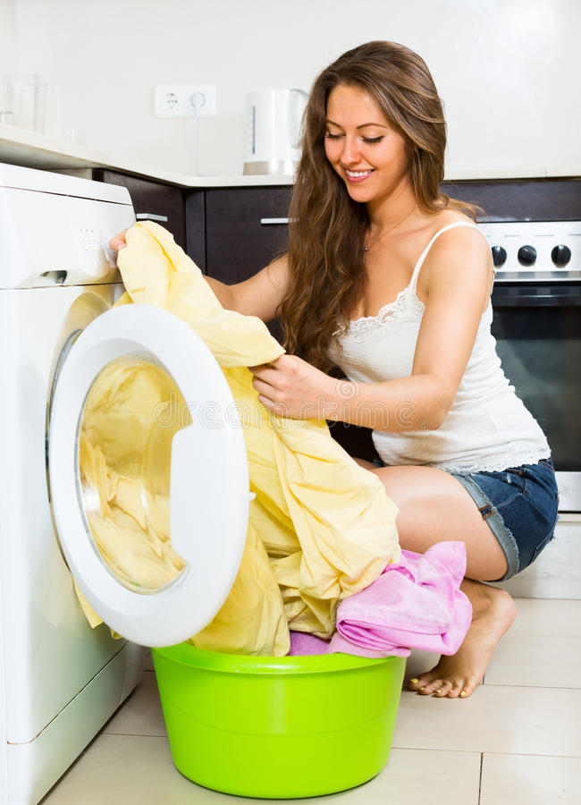 相当在洗衣机的少妇洗涤的衣裳 免版税库存图片