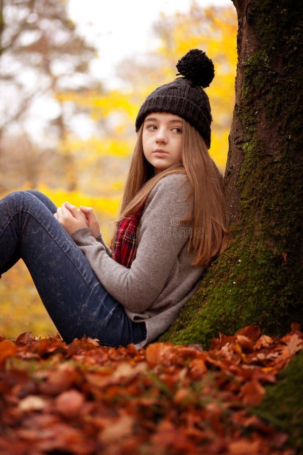 相当坐反对一棵树的女孩在秋天 库存照片