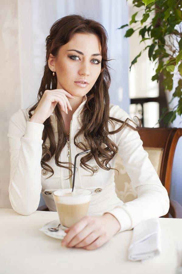 相当坐在与一杯茶的咖啡馆的少妇 库存照片