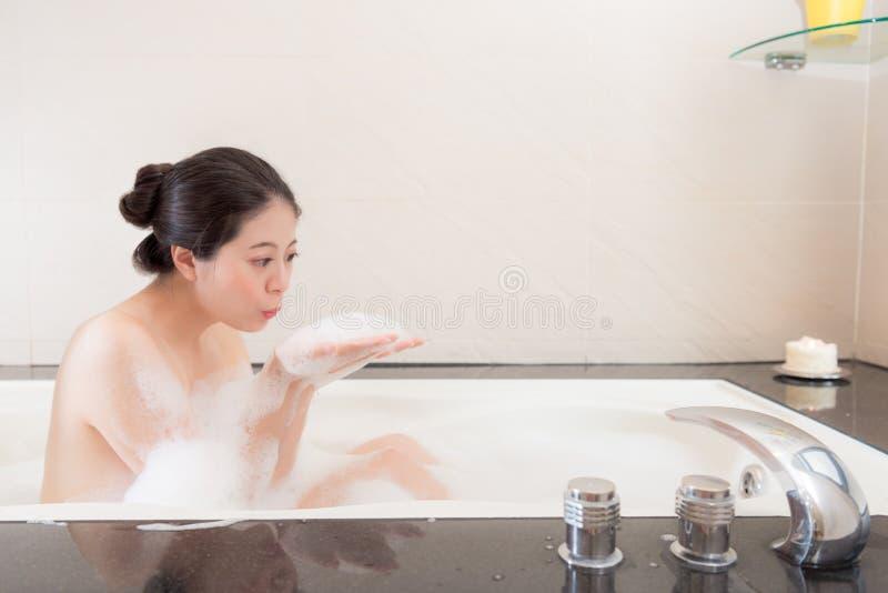 相当坐在浴缸沐浴的可爱的妇女 库存图片