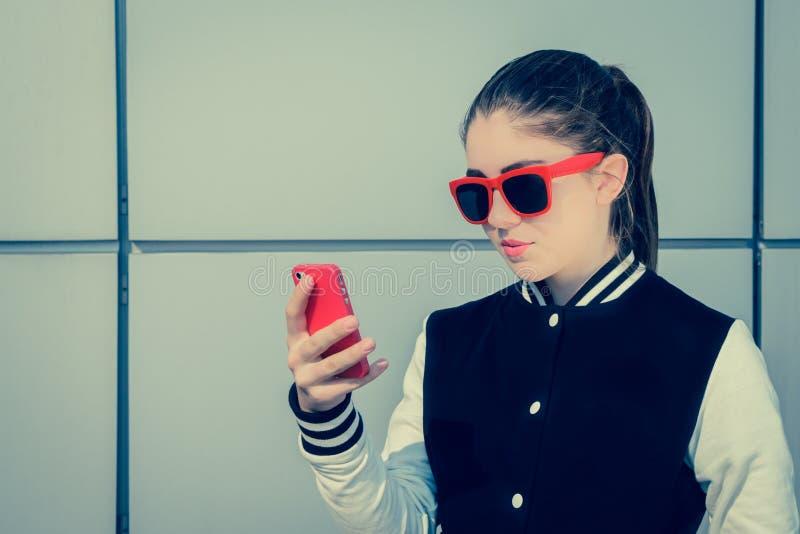 相当太阳镜的十几岁的女孩使用她巧妙的电话 免版税库存照片