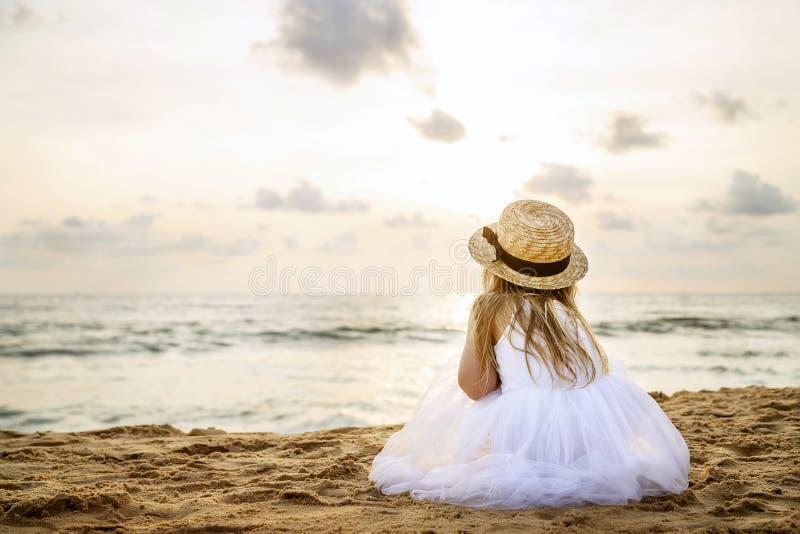 相当女孩从后面与在草帽和一件白色芭蕾舞短裙礼服的长的金发坐夏天海滩 免版税库存照片