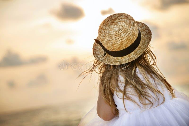 相当女孩从后面与在草帽和一件白色芭蕾舞短裙礼服的长的金发坐夏天海滩 免版税库存图片