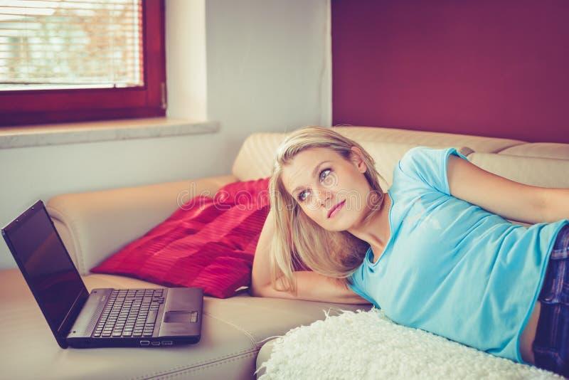 相当女孩在沙发说谎由她的膝上型计算机 免版税库存照片